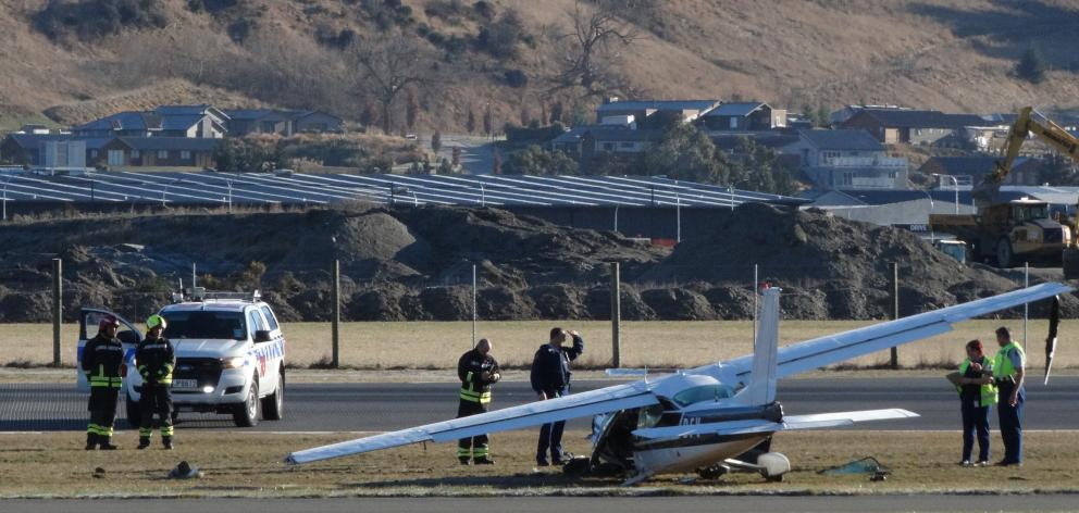 Police and Queenstown Airport fire rescue staff examine a Cessna 177 that crashed just after take-off at the airport yesterday. Photo: Guy Williams