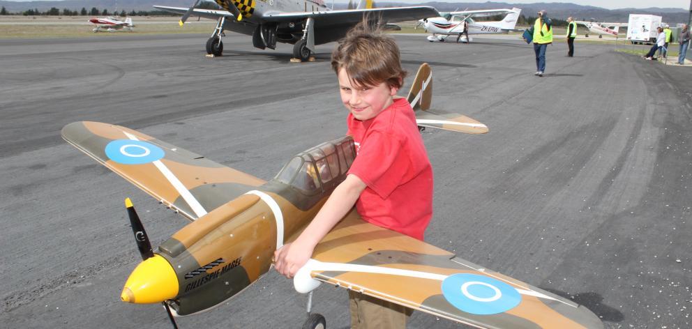 Flynn Millar (9), of Alexandra, holds a model Curtiss P-40N Kittyhawk at the Wings 'n' Wheels...