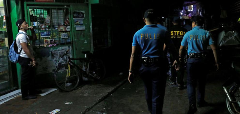 Policemen from Caloocan Police District patrol a dimly lit alley at a residential district in Caloocan City Metro Manila. Photo: Reuters