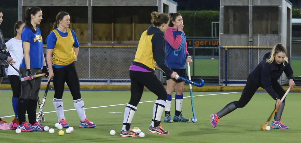 Southern Storm's Emily McNaughtan pushes the ball forward, with  team mates Alice Sharples (left)...