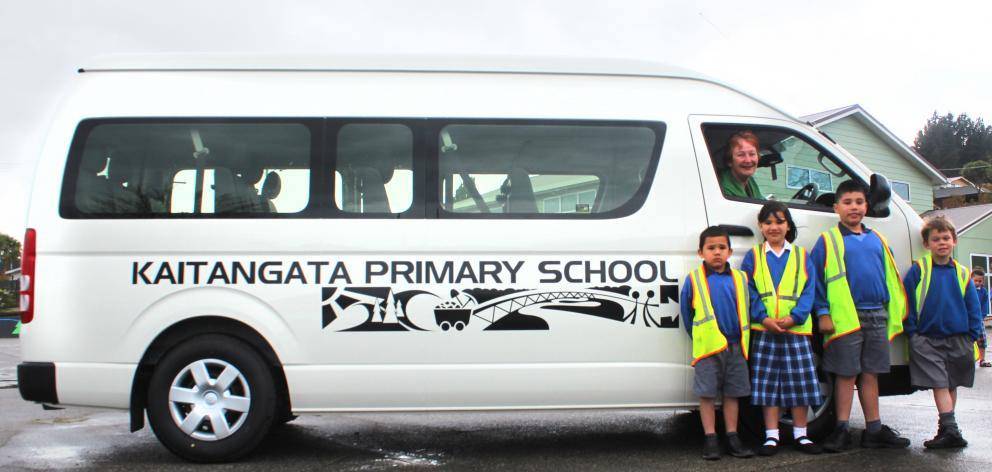 Kaitangata Primary School pupils (from left) Martin (5), Jess (7) and Freddy Daumann (8) with Evan Anderson (6) and school principal Anneta Payne (driver window) have a reason to celebrate now the school has its own minibus to transport pupils. Photo: Sam