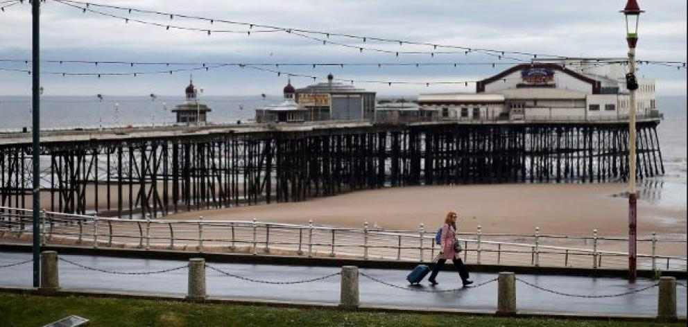 A woman pulls her suitcase past the North Pier in Blackpool, Britain. Photo: Reuters