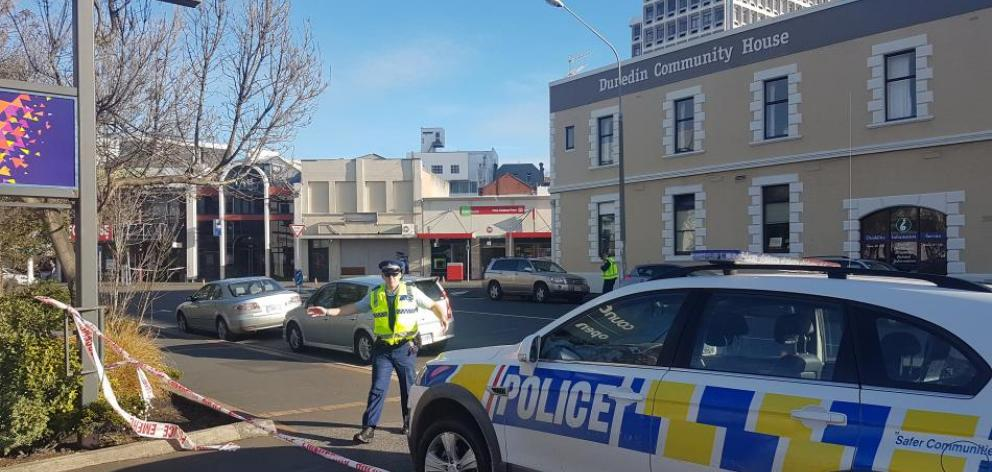 A Dunedin police officer asking people that get back from the cordon at Moray Pl. Photo: ODT