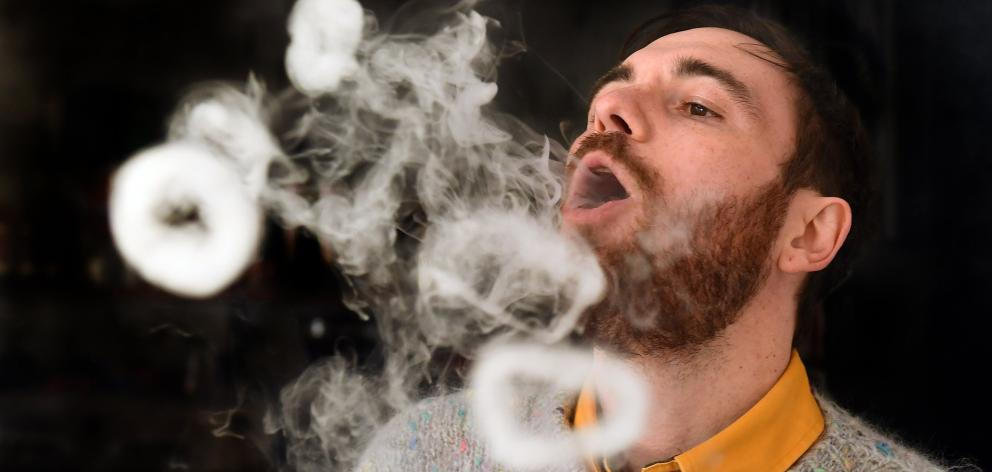 Dunedin e-cigarette store Vapourium account manager Cody Peneamene blows vapour rings from a...