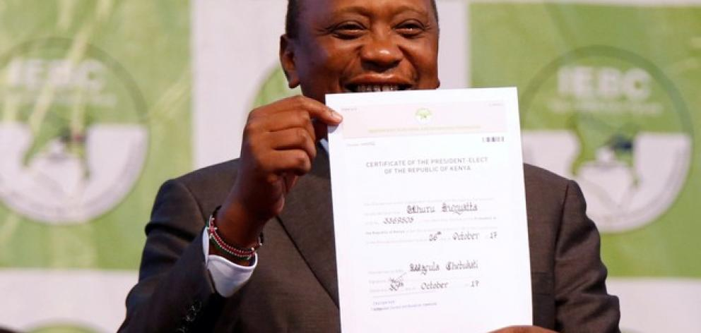 Incumbent President Uhuru Kenyatta holds the certificate of President-Elect of the Republic of Kenya after he was announced winner of the repeat presidential election. Photo: Reuters