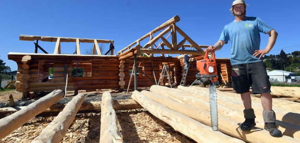 Mat Rusher with the log cabin he has built, and is about to deconstruct. Photo: Stephen Jaquiery