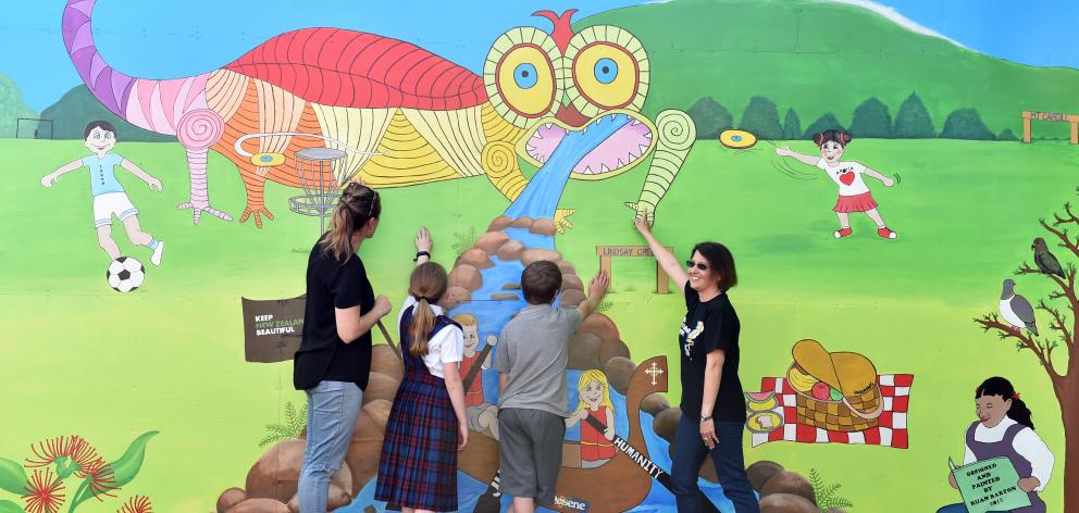 Sacred Heart School teacher aide and artist Ruan Barton (right) explains the inspiration behind...