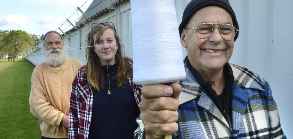 Wellington artist Barry Thomas (front) runs a piece of string around Dunedin with the help of...