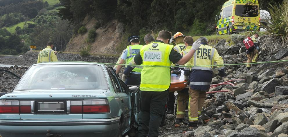 Emergency services carry a man to an ambulance after he suffered a medical event while driving. Photo: Christine O'Connor