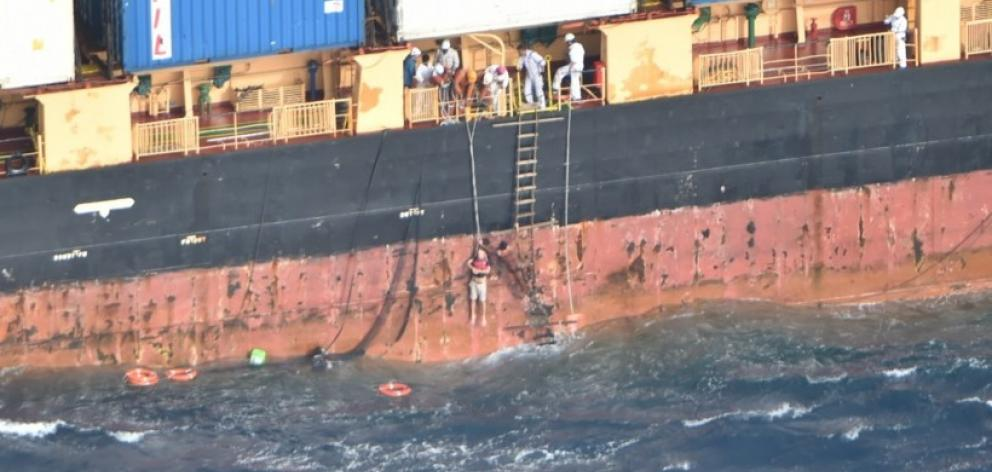 A dramatic photo released by the NZDF shows the stricken Norwegian sailor being hoisted up the side of MV Southern Lily by crew as a life ring bobs in the large swells below him. Photo: NZDF