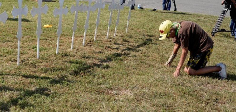 Brandy Jones prays in front of 26 crosses erected near the site of the shooting at the First Baptist Church of Sutherland. Photo: Reuters