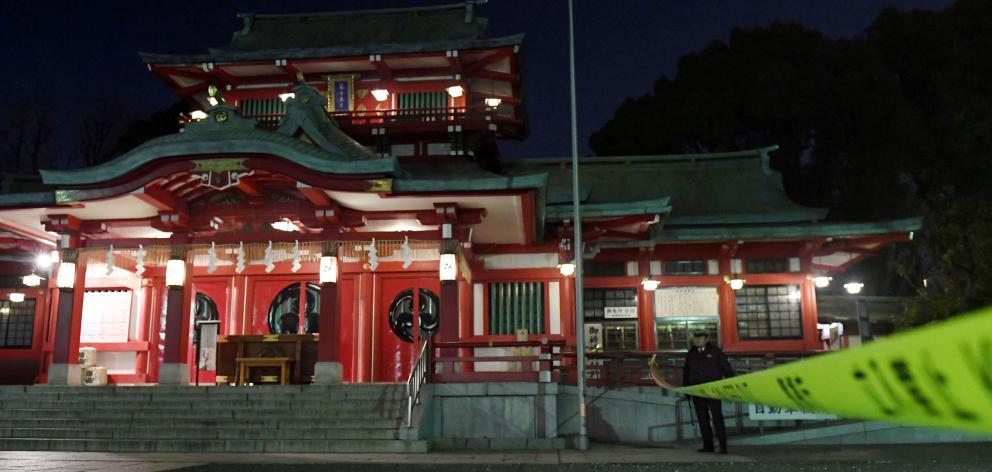 A policeman stands guard in front of the main temple of the Tomioka Hachimangu shrine in Tokyo, Japan. Photo:  Kyodo/via REUTERS
