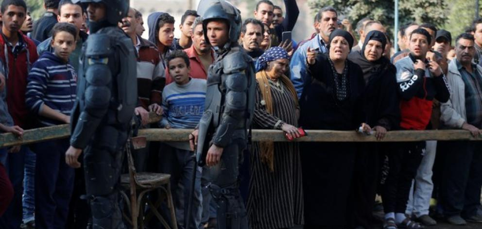 People gather at the site of attack on a church in the Helwan district south of Cairo. Photo: Reuters