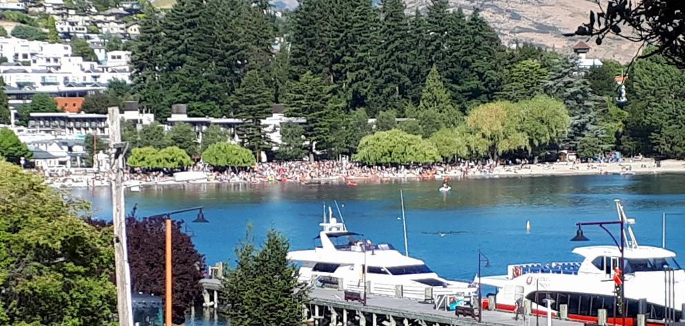 Christmas revellers bask in the sunshine as they swarm Queenstown lakefront. Photo: Louise Scott