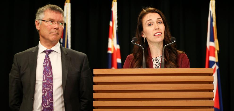 Prime Minister Jacinda Ardern speaks while Minister for Economic Development David Parker looks...