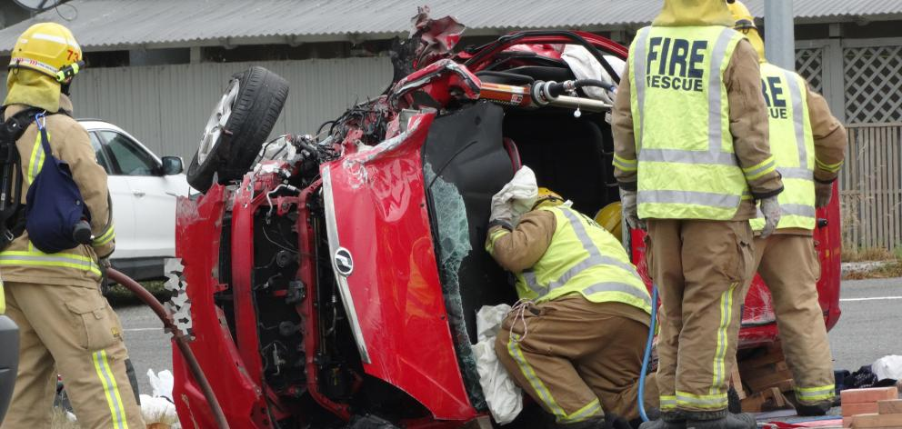 Firefighters work  to free two people trapped in a vehicle involved in a two-vehicle crash at...