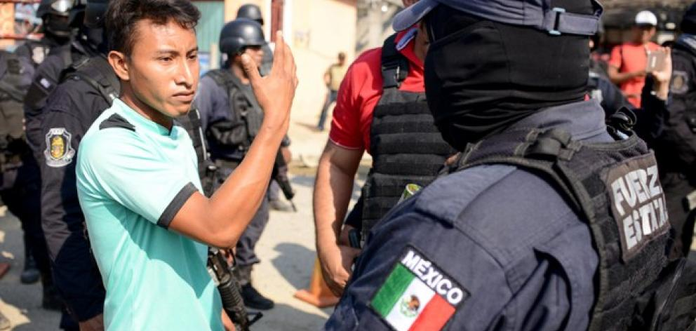 A relative argues with a police officer, near where an exchange of gunfire took place between residents and members of a local, self-appointed community police force which according to local media, left 11 dead in La Concepcion. Photo: Reuters