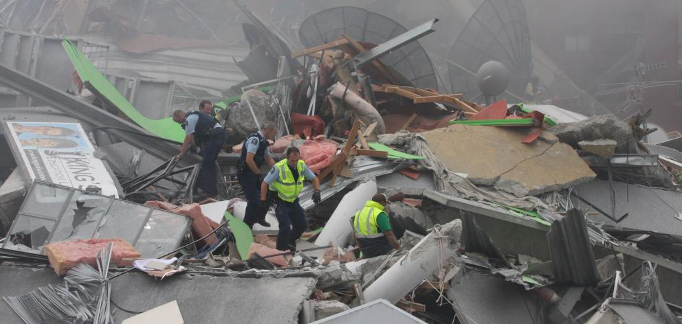 Emergency services and volunteers rescue people from the collapsed CTV building. Photo: Geoff Sloan
