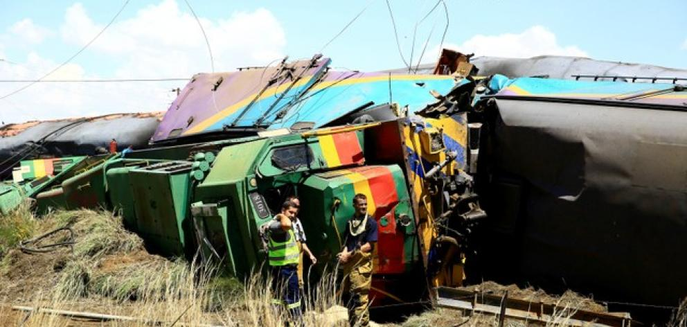 Workers stand next to a wreckage after a train crash near Hennenman in the Free State province. Photo: Reuters