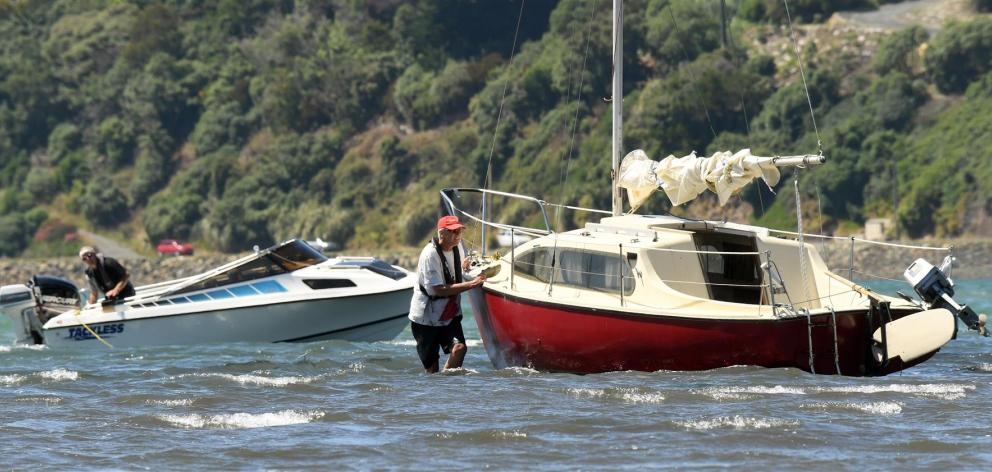 Brent Young (left, in power boat) prepares to tow a stricken yacht off a mud-bed near the entrance to the Otago Yacht Club where it drifted after its motor broke down yesterday. The yachtsman (right), who only wanted to be known as John, was pleased when