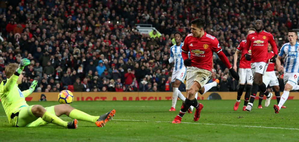 Manchester United's Alexis Sanchez scores their second goal from a rebound after having his...