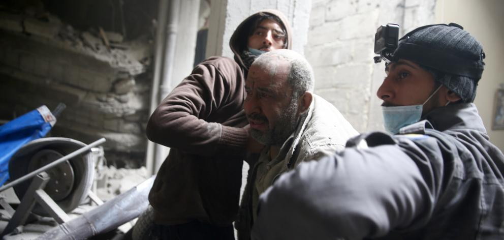 Civil defence personnel help a man from a shelter in the besieged town of Douma in eastern Ghouta...