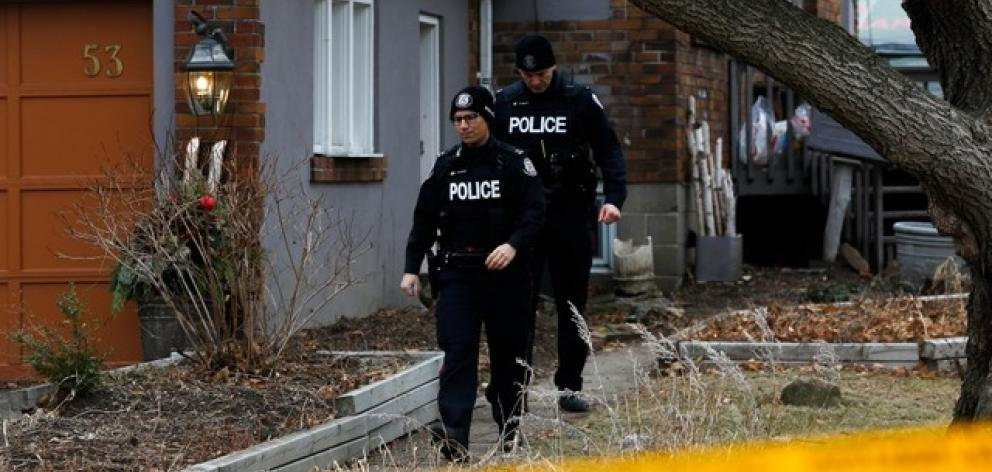 Police officers guard the grounds of a house they had searched in Toronto. Photo: Reuters