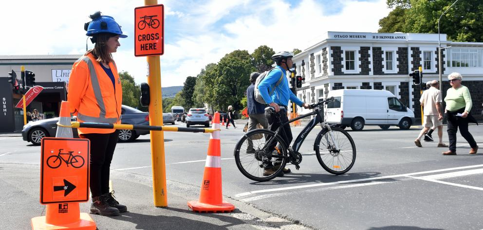 Under the watchful eye of Lydia Perkins, of Fulton Hogan, NZ Transport Agency project manager Simon Underwood wheels his e-bike across Great King St to reach the revamped section of cycleway. Photo: Peter McIntosh