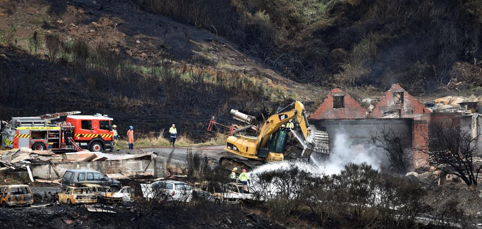 Firefighters dampen down hot spots yesterday with help from earthmoving machinery, following the...