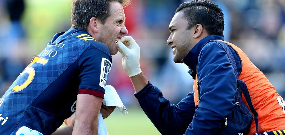 Ben Smith, of the Highlanders, receives treatment for his tooth during the match.