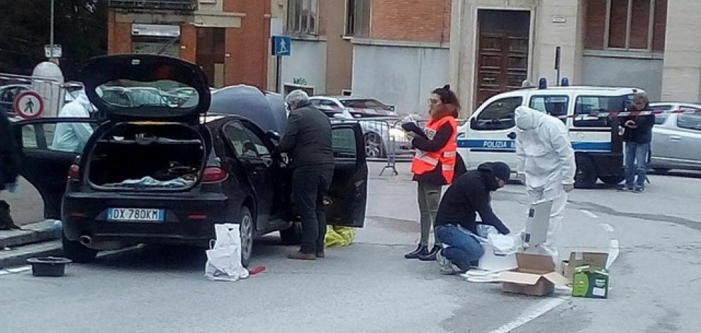 Forensics inspect a car used by a gunman in Macerata. Photo: Reuters