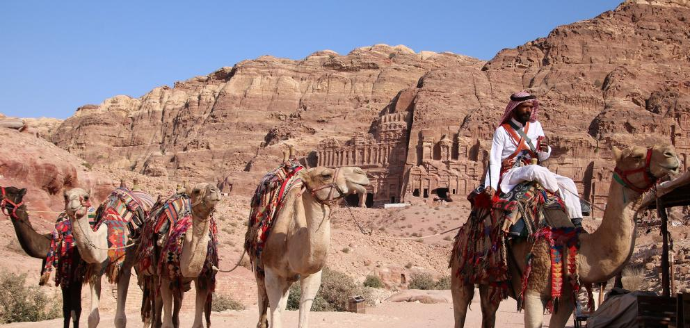 A Bedouin camel herder waits for ride-takers in the ancient rock city of Petra.