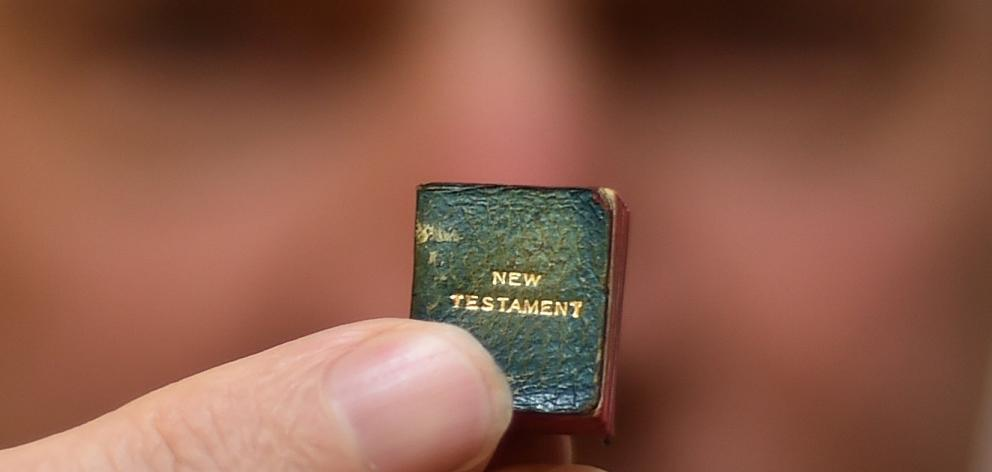 Dunedin librarian Julian Smith holds what could be the world's smallest printed New Testament...