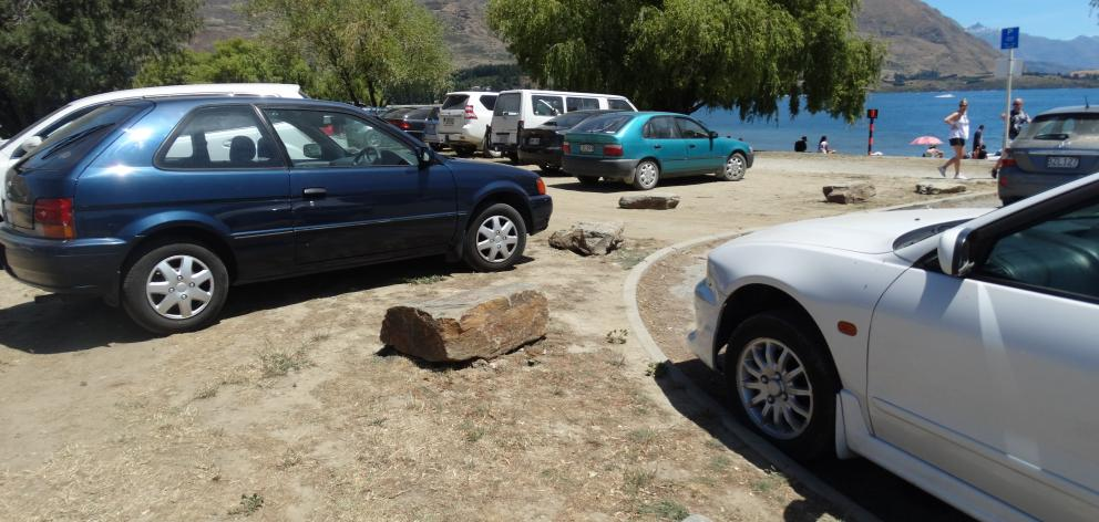 Rocks placed at the edge of grassy areas along Wanaka's lakefront to prevent parking were moved...