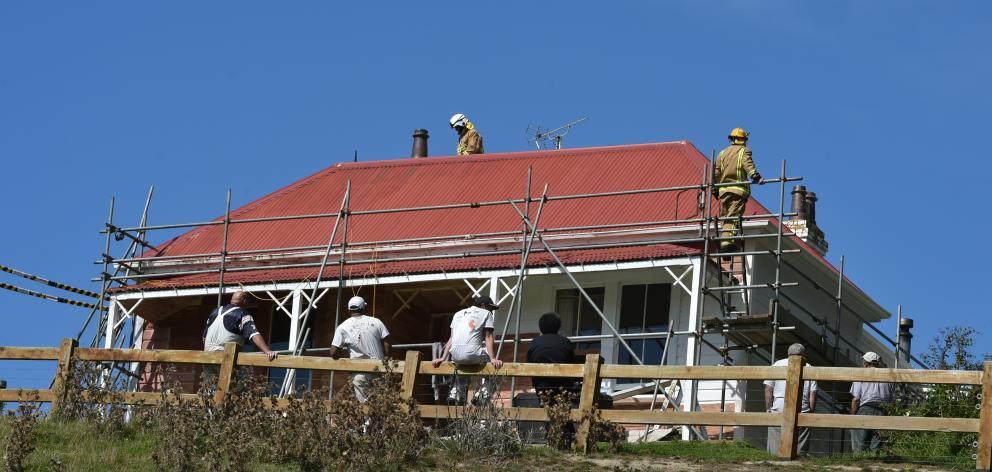 Painters watch as firefighters inspect the house that featured in the Robin White work A Buzzy Bee for Siulolovao after a fire started in its roof space yesterday. Photo: Gregor Richardson
