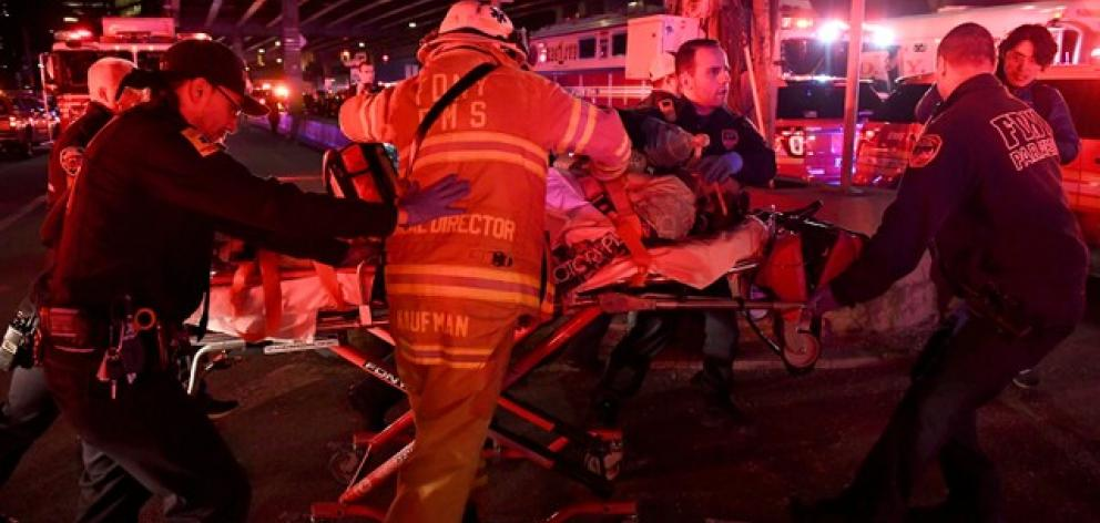 Paramedics and members of the FDNY perform CPR on a victim of a helicopter that crashed into the East River in New York. Photo: Reuters