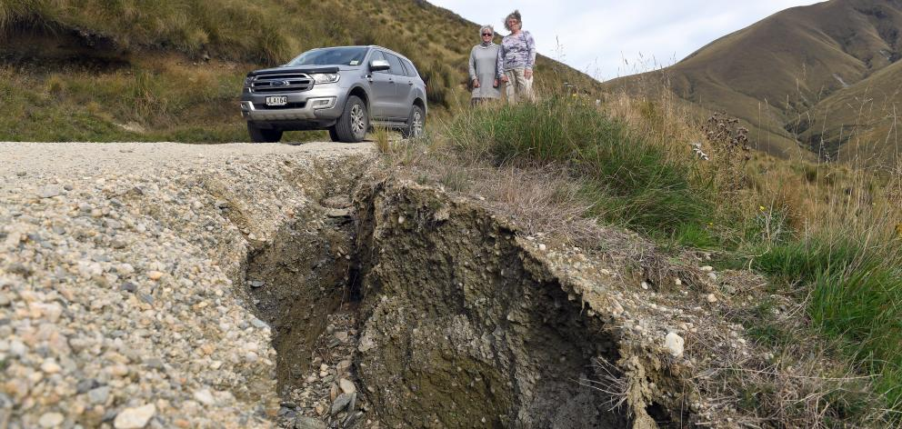 Danseys Pass residents Mary Hore (left) and Jo Todd inspect the washed-out mountain pass road....
