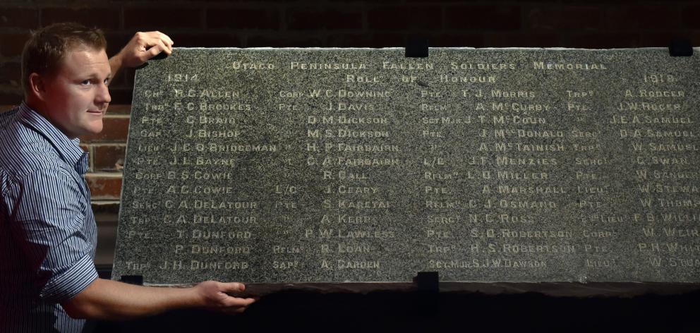 Toitu Otago Settlers Museum exhibition developer William McKee displays the granite slab engraved...