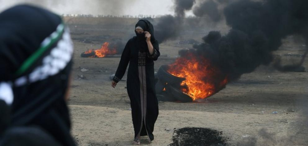 A female Palestinian demonstrator walks during a at the Israel-Gaza border. Photo: Reuters