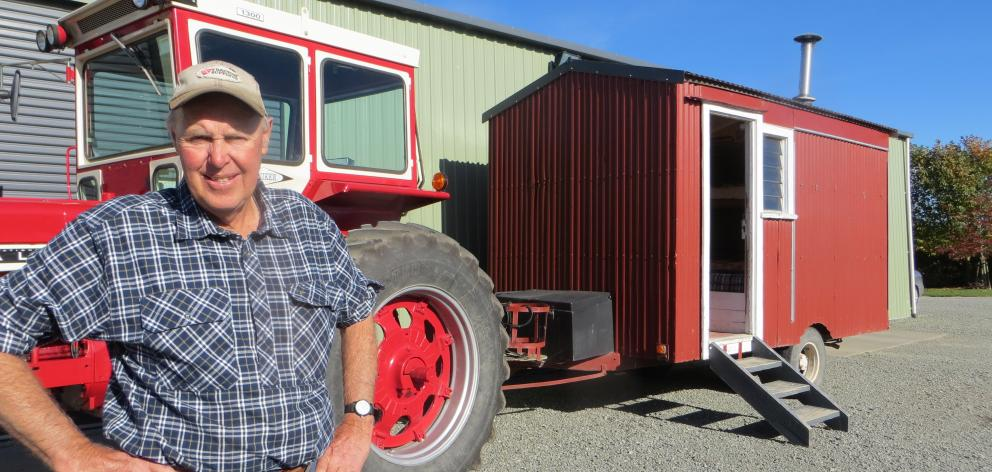 Ashburton Vintage Machinery Club president John Hall stands next to the little red corrugated...