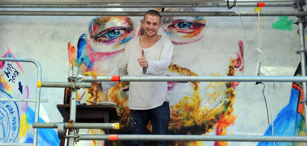 Artist Tyler Kennedy Stent stands between the eyes of Ed Sheeran, a controversial mural he was...