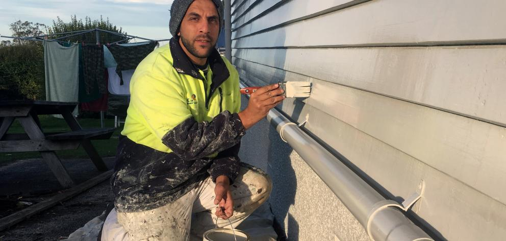 Dunedin Housing Maintenance Contractors brush hand and former refugee Mohammed Ali paints a state house in Halfway Bush. PHOTO: SHAWN MCAVINUE
