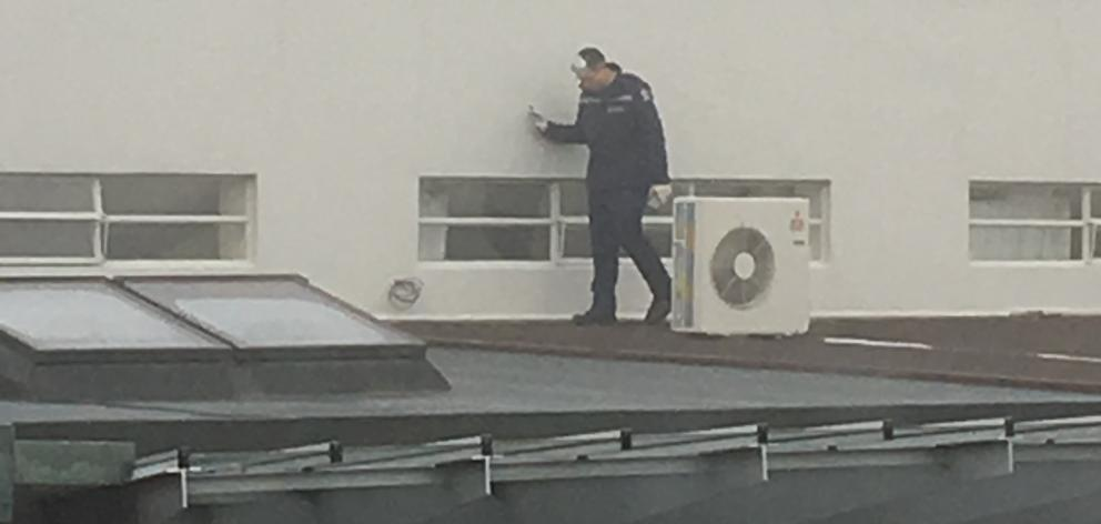 A policeman on the roof of the Alexandra Community Centre and Memorial Theatre yesterday morning...