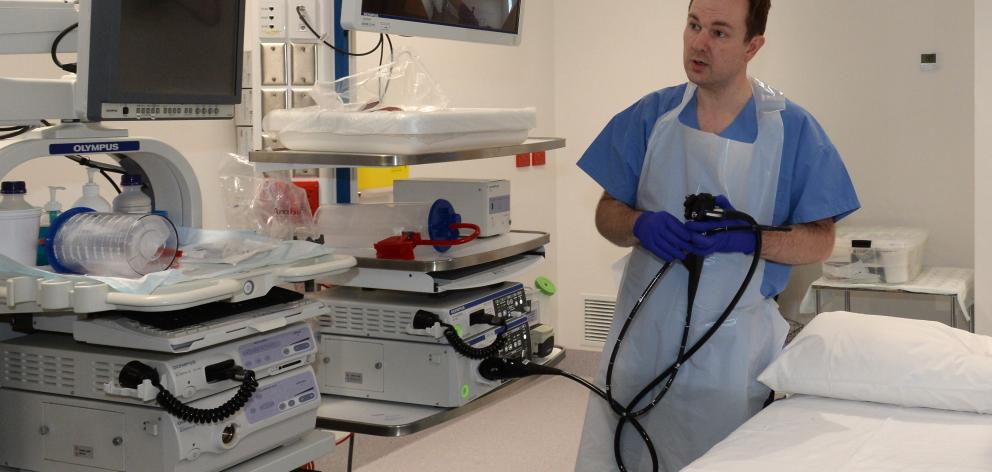 Gastroenterology clinical director Dr Jason Hill holds a gastroscope in one of the procedure...