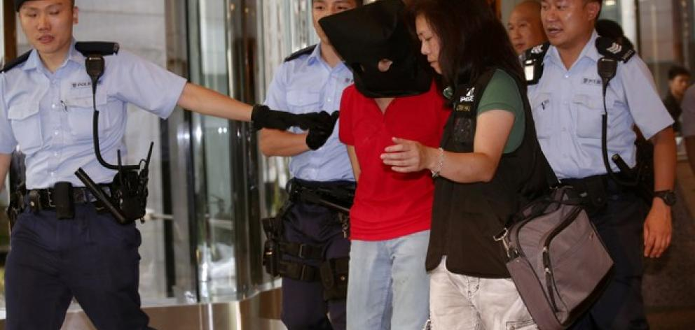 A female suspect is arrested by police officers after a woman opened fire and wounded four people at a park outside Taikoo Shing in Hong Kong. Photo: Reuters