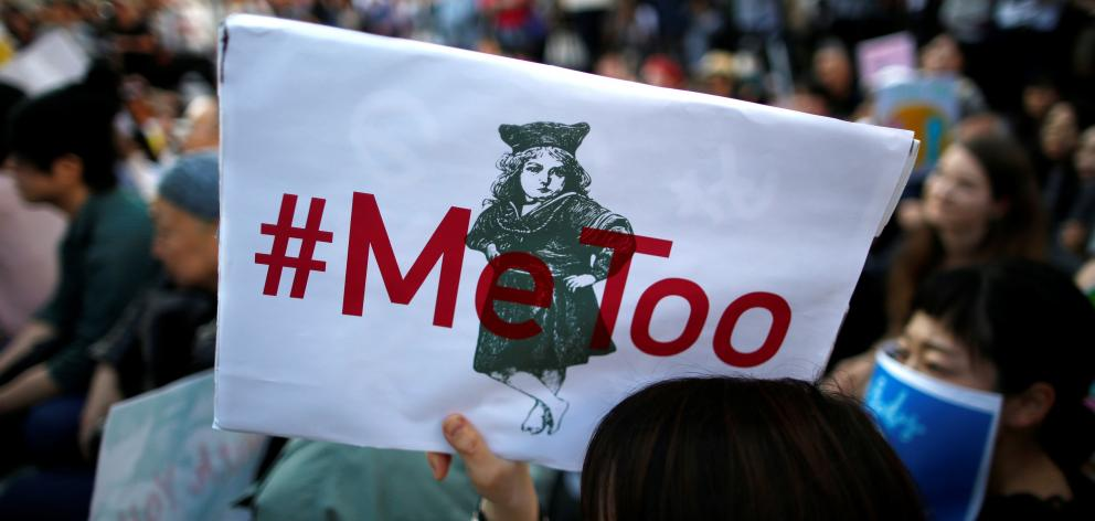 """A protester raises a placard reading """"#MeToo"""" during a rally against harassment in Tokyo. Photo: Reuters"""