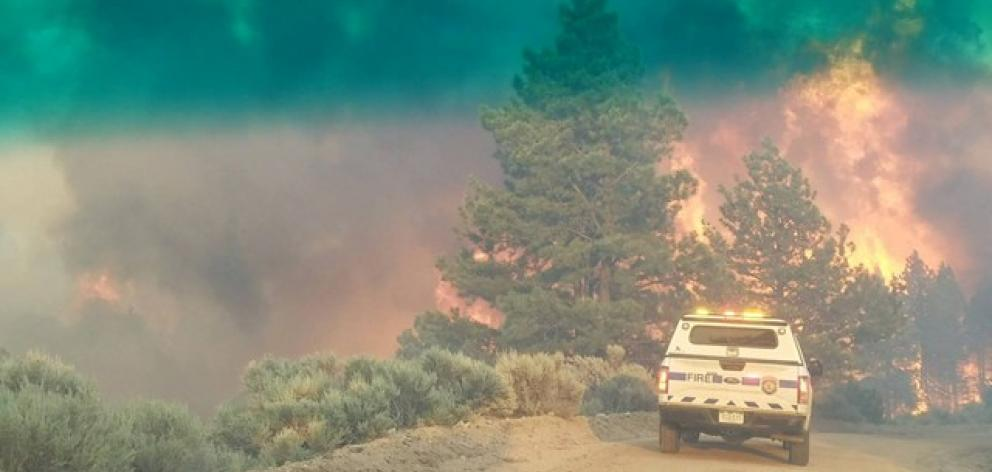 Flames rise from a treeline near an emergency vehicle during efforts to contain the Spring Creek Fire. Photo: Costilla County Sheriff's Office via  Reuters