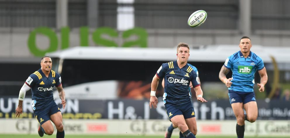 Highlanders midfield back Tei Walden looks towards the ball while Aaron Smith (left) and Sonny Bill Williams look on at Forsyth Barr Stadium in February. Photo: Gregor Richardson