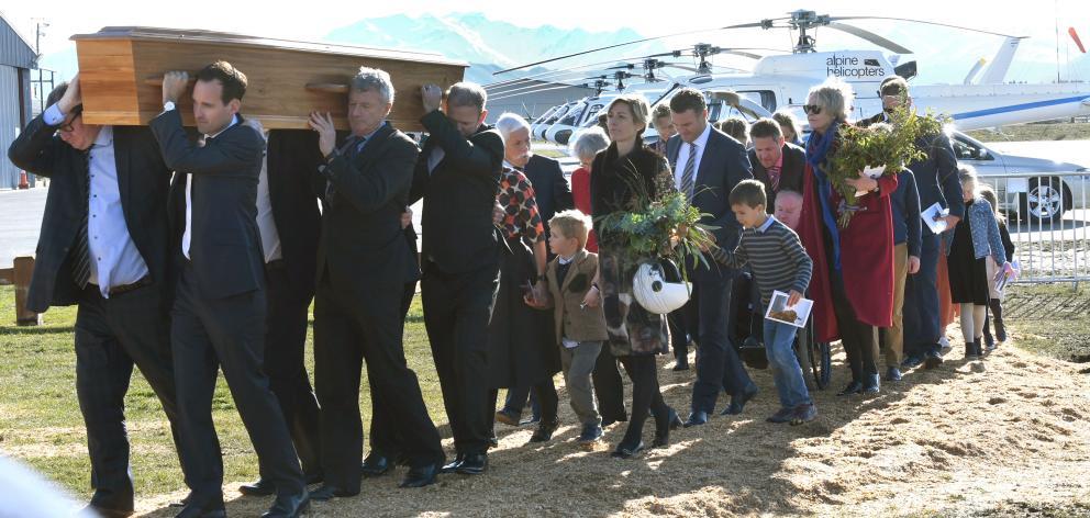 Alice Wallis holds her husband's flying helmet as pallbearers carry Matthew Wallis' coffin into...