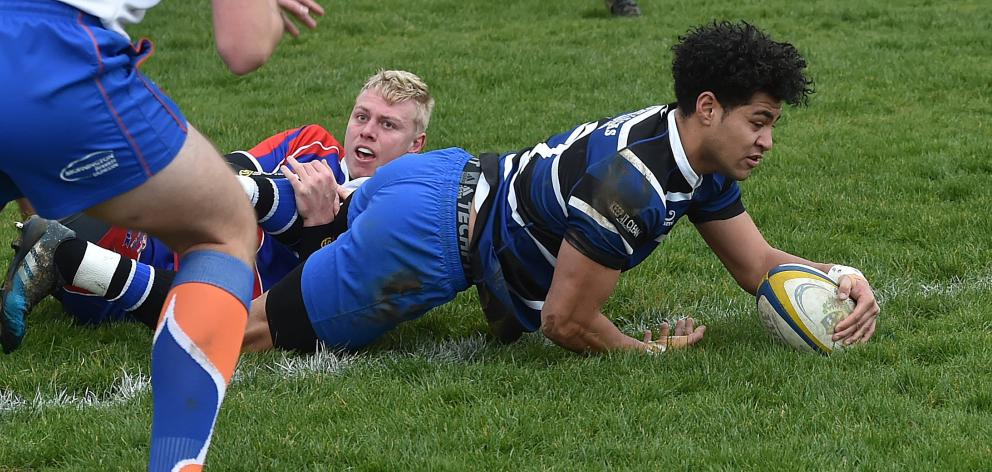 Kaikorai midfielder TeeJay Ane goes over for a try in the tackle of Harbour first five-eighth...